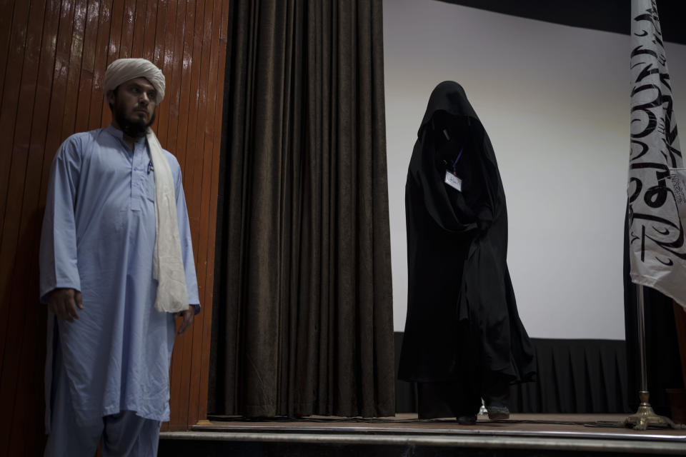 A woman walks down from the stage inside an auditorium at Kabul University's education center during a demonstration in support of the Taliban government in Kabul, Afghanistan, Saturday, Sept. 11, 2021. (AP Photo/Felipe Dana)