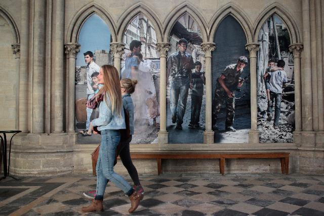 People walk in the Cathedral of Bayeux during an exhibition dedicated to the work of French photojournalist Laurent Van Der Stockt in Syria, on October 11, 2014 in Bayeux (AFP Photo/Charly Triballeau)