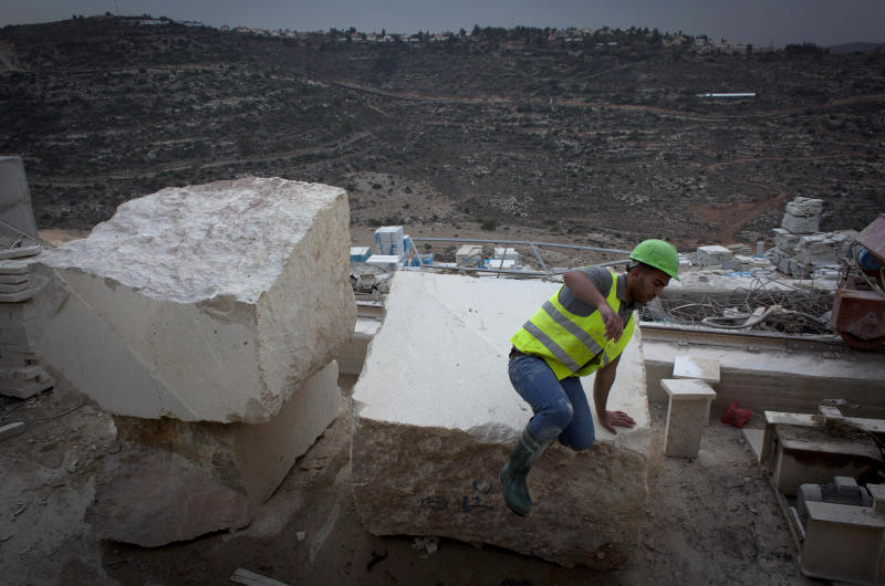 In this photo taken Dec. 3, 2013, a Palestinian works at a site facing the neighboring Israeli settlement of Ateret, in the background, at the under-construction Palestinian city of Rawabi, north of the West Bank city of Ramallah. A state-of-the art Palestinian city under construction in the West Bank, with residential towers, parks, an outdoor mall and a convention center has become a symbol of national pride. (AP Photo/Nasser Nasser)