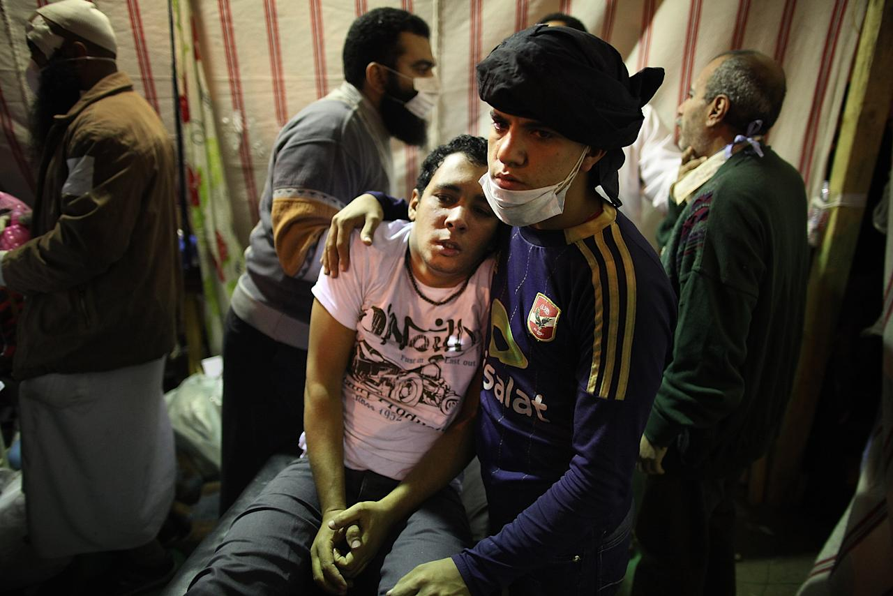 CAIRO, EGYPT - NOVEMBER 22:  A protestor suffering from the effects of tear gas is comforted  in a make shift medical centre in Tahrir Square on November 22, 2011 in Cairo, Egypt. Thousands of Egyptians have been gathering in Tahrir Square after three days of deadly clashes with security forces despite a promise from Egypt's interim ruling Military council to bring forward Presidential elections. (Photo by Peter Macdiarmid/Getty Images)