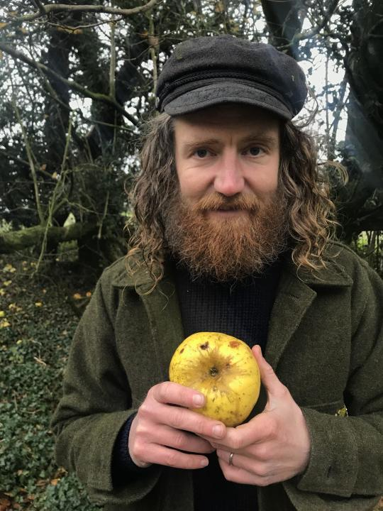 Archie Thomas holding his apple find in woodlands near his home (Hannah Thomas/PA)
