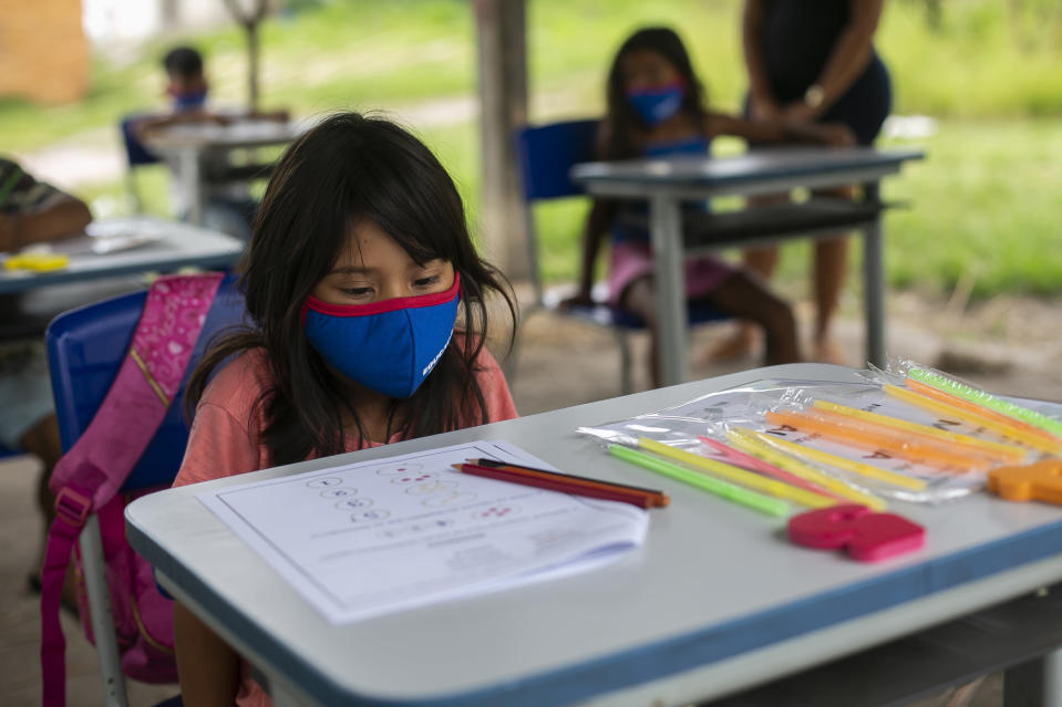 A Guarani girl, wearing a protective face mask, sits at her desk in an open air classroom in the Mata Verde Bonita village, in Marica, Rio de Janeiro state, Brazil, Thursday, Feb. 25, 2021, where healthcare workers are making the rounds with coolers containing doses of China's Sinovac COVID-19 vaccine as part of a mass immunization program aimed at inoculating all of Rio's 16 million residents by the end of the year. (AP Photo/Bruna Prado)