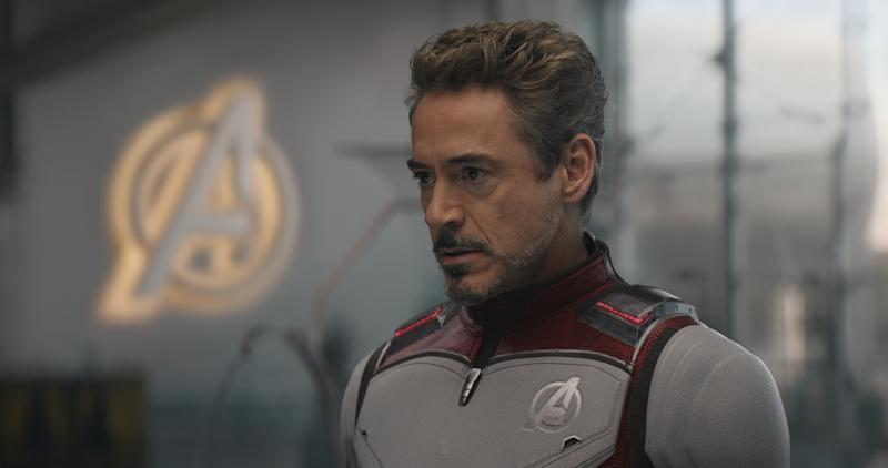 Iron Man with a serious face standing in front of a lighted Avengers logo.