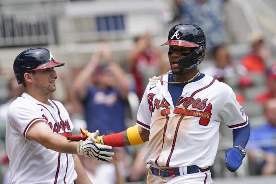 Atlanta Braves' Ronald Acuna Jr., right, is greeted at home plate by Austin Riley after scoring on an Ozzie Albies' base hit in the sixth inning of a baseball game against the Washington Nationals, Thursday, June 3, 2021, in Atlanta. (AP Photo/John Bazemore)