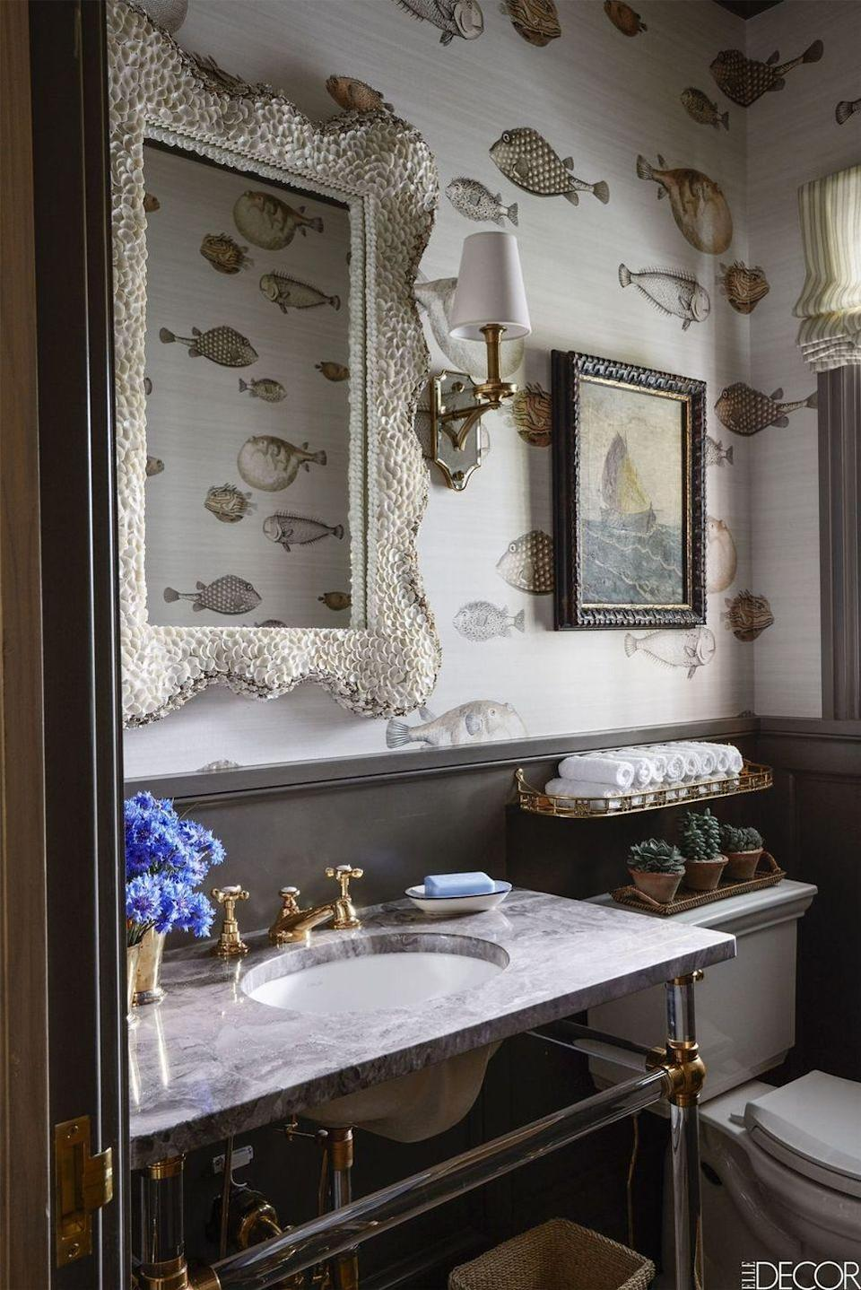 """<p>A <a href=""""https://www.elledecor.com/design-decorate/house-interiors/a8631/most-beautiful-homes-in-east-hampton/"""" rel=""""nofollow noopener"""" target=""""_blank"""" data-ylk=""""slk:beach house in the Hamptons"""" class=""""link rapid-noclick-resp"""">beach house in the Hamptons</a> really leans into the nautical look with fish-printed wallpaper by Cole & Son. The powder room mirror is by Made Goods and the sconce is by Visual Comfort.</p><p><em>Cole & Son Acquario Wallpaper, $330</em><br><a class=""""link rapid-noclick-resp"""" href=""""https://www.mahoneswallpapershop.com/product/9710030-acquario-pal-bl-mlt-cole-and-son?gclid=CjwKCAjw8NfrBRA7EiwAfiVJpZt8JNdQZzDYmiS7TsLyusdqXfs5KSEWL6E6PvZUAzAeOyiDzRXDcRoCNKwQAvD_BwE"""" rel=""""nofollow noopener"""" target=""""_blank"""" data-ylk=""""slk:Shop the Look"""">Shop the Look</a></p>"""