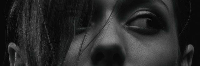 black and white photo of young woman close up looking out of corner of her eye