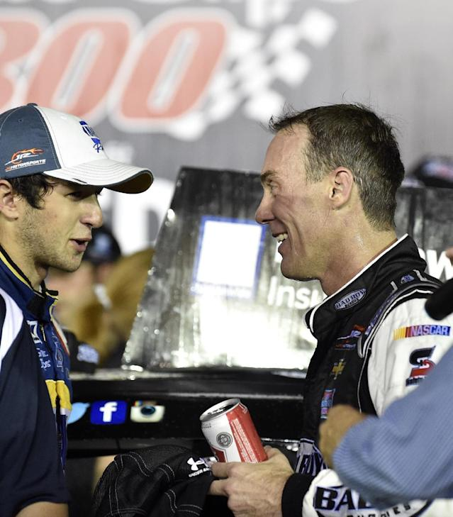 Nationwide Series driver Chase Elliott, left, congratulates winner Kevin Harvick, right, in victory lane after the NASCAR Nationwide Cup Series Great Clips 300 auto race at Atlanta Motor Speedway, Saturday, Aug. 30, 2014 in Hampton, Ga. (AP Photo/David Tulis)