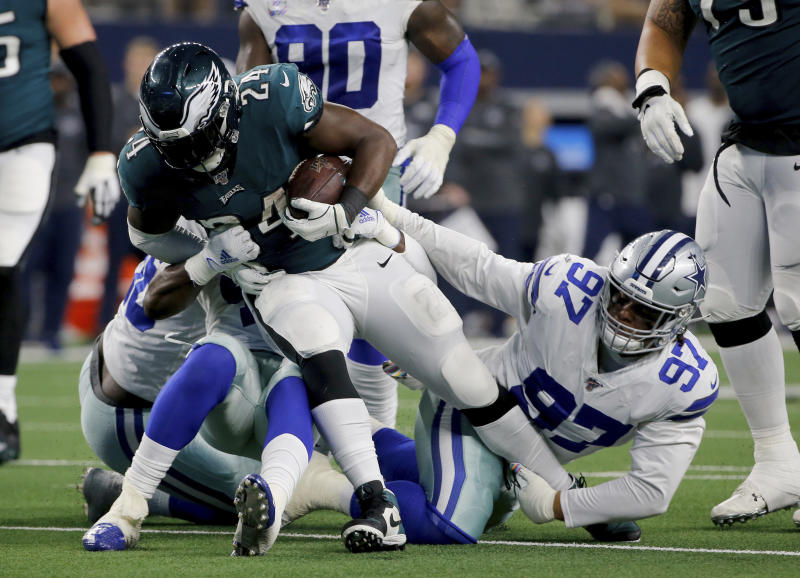 Philadelphia Eagles running back Jordan Howard (24) attempts to break through a tackle by Dallas Cowboys' Trysten Hill (97) in the second half of an NFL football game in Arlington, Texas, Sunday, Oct. 20, 2019. (AP Photo/Michael Ainsworth)