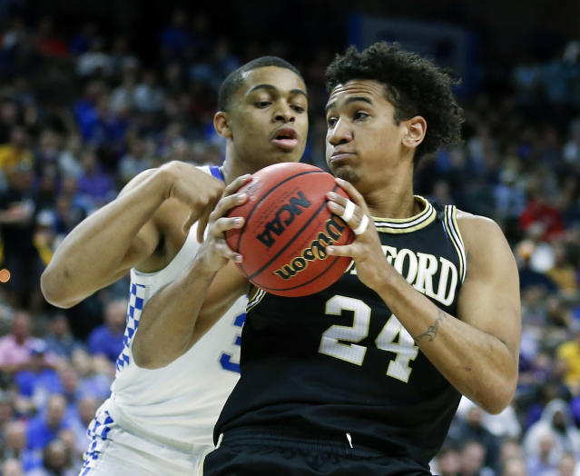 Wofford forward Keve Aluma (24) looks for a path to the basket against Kentucky's Keldon Johnson during the first half of a second-round game in the NCAA mens college basketball tournament in Jacksonville, Fla., Saturday, March 23, 2019. (AP Photo/Stephen B. Morton)
