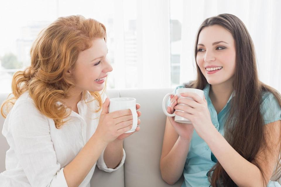 Women talking on couch drinking cups of coffee or tea