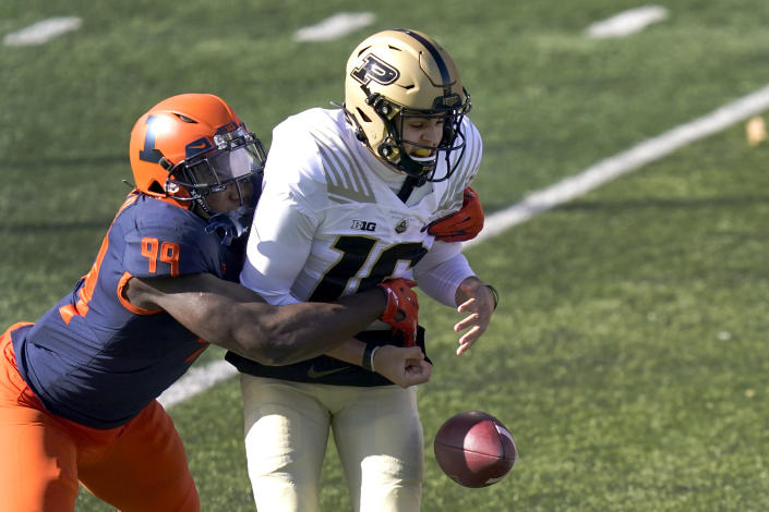 Illinois defensive lineman Owen Carney Jr., left, strips Purdue quarterback Aidan O'Connell of the ball during the first half of an NCAA college football game Saturday, Oct. 31, 2020, in Champaign, Ill. (AP Photo/Charles Rex Arbogast)