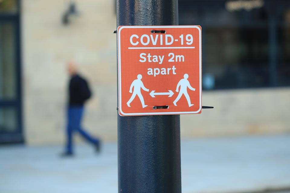 A sign advising people to stay two metres apart on a lamppost in the centre of Bradford, West Yorkshire, one of the areas where new measures have been implemented to prevent the spread of coronavirus. Stricter rules have been introduced for people in Greater Manchester, parts of East Lancashire, and West Yorkshire, banning members of different households from meeting each other indoors.