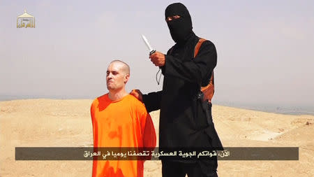 Still image from undated video of a masked Islamic State militant holding a knife speaking next to man purported to be James Foley at an unknown location