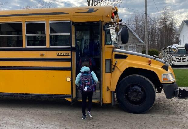 Kids hop on a school bus for the first time in two months in May 2020. The driver sits behind a plastic screen, wearing a mask. (Kimberley Molina/CBC - image credit)