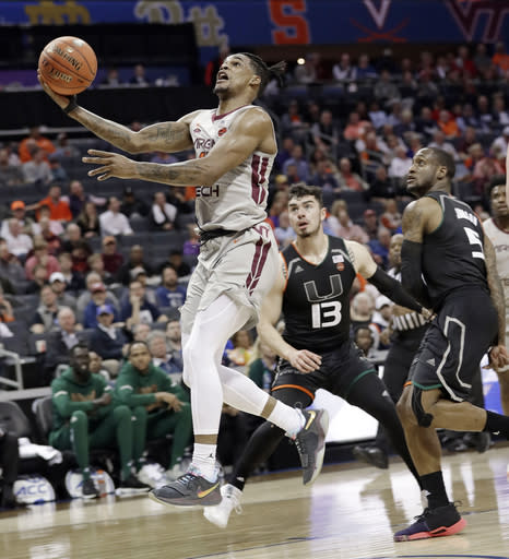Virginia Tech's Ahmed Hill, left, drives past Miami's Anthony Mack (13) and Zach Johnson (5) during the first half of an NCAA college basketball game in the Atlantic Coast Conference tournament in Charlotte, N.C., Wednesday, March 13, 2019. (AP Photo/Chuck Burton)