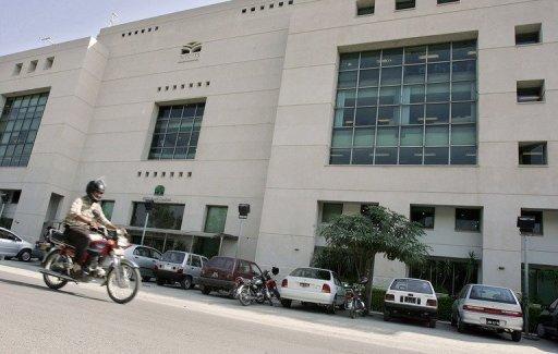 A Pakistani man rides his motorbike in front of the building of the Muslim Commercial Bank