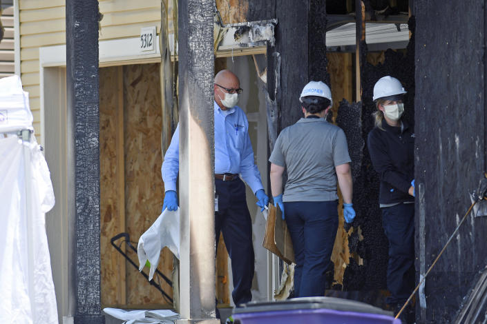 Investigators examine the remnants of a house fire that killed five people in suburban Denver on Wednesday, Aug. 5, 2020. Three people escaped the fire by jumping from the home's second floor. Investigators believe the victims were a toddler, an older child and three adults. Authorities suspect the fire was intentionally set. (AP Photo/Thomas Peipert)