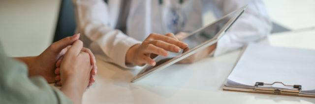 doctor showing patient information on a tablet