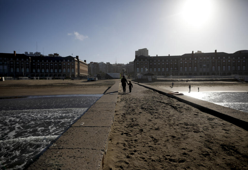 A woman and child walk along the coast during the COVID-19 pandemic in Mar del Plata, Argentina, Saturday, Oct. 10, 2020. The resort's new reality is starkly visible: Its beaches and businesses are deserted at a time when Argentines normally would be booking lodging and renting beach gear for the fast-approaching Southern Hemisphere summer. (AP Photo/Natacha Pisarenko)