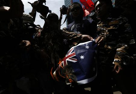 Protesters burn an Australian flag during a protest in front of the Australia embassy in Jakarta, November 21, 2013. Australia warned travellers to Indonesia of a planned demonstration at its embassy in Jakarta on Thursday as anger grows over reports Canberra spied on top Indonesians, including the president and his wife. REUTERS/Beawiharta