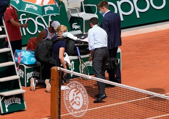 Ashleigh Barty talks to medical personnel at the end of the first set