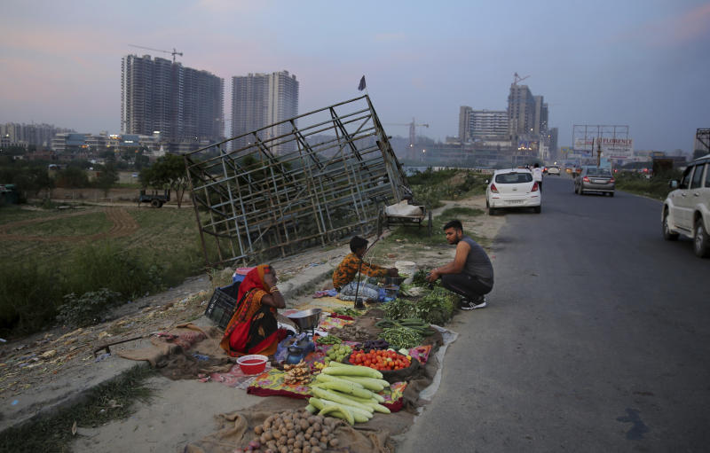 In this Thursday, Sept. 5, 2019, photo, a roadside vegetable seller waits for customers in Noida on the outskirts of New Delhi, India. Confidence in the Indian economy is giving way to uncertainty as growth in the labor-intensive manufacturing sector has come to a near standstill, braking to 0.6% in the last quarter from 12.1% in the same period a year earlier. (AP Photo/Altaf Qadri)