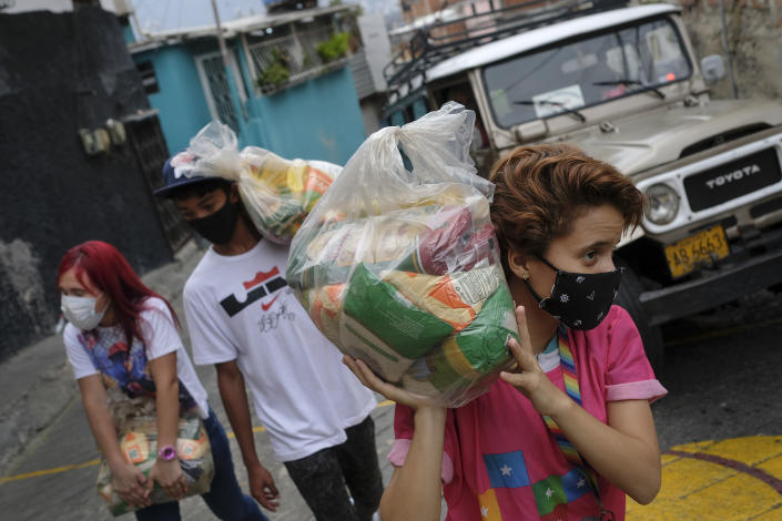 Youth carry bags of basic food staples, such as pasta, sugar, flour and kitchen oil, provided by a government food assistance program, to delivery it in the Santa Rosalia neighborhood of Caracas, Venezuela, Saturday, April 10, 2021. The program known as Local Committees of Supply and Production, CLAP, provides subsidized food for vulnerable families, especially now in the midst of a quarantine to stop the COVID-19 pandemic that has left many without income. (AP Photo/Matias Delacroix)