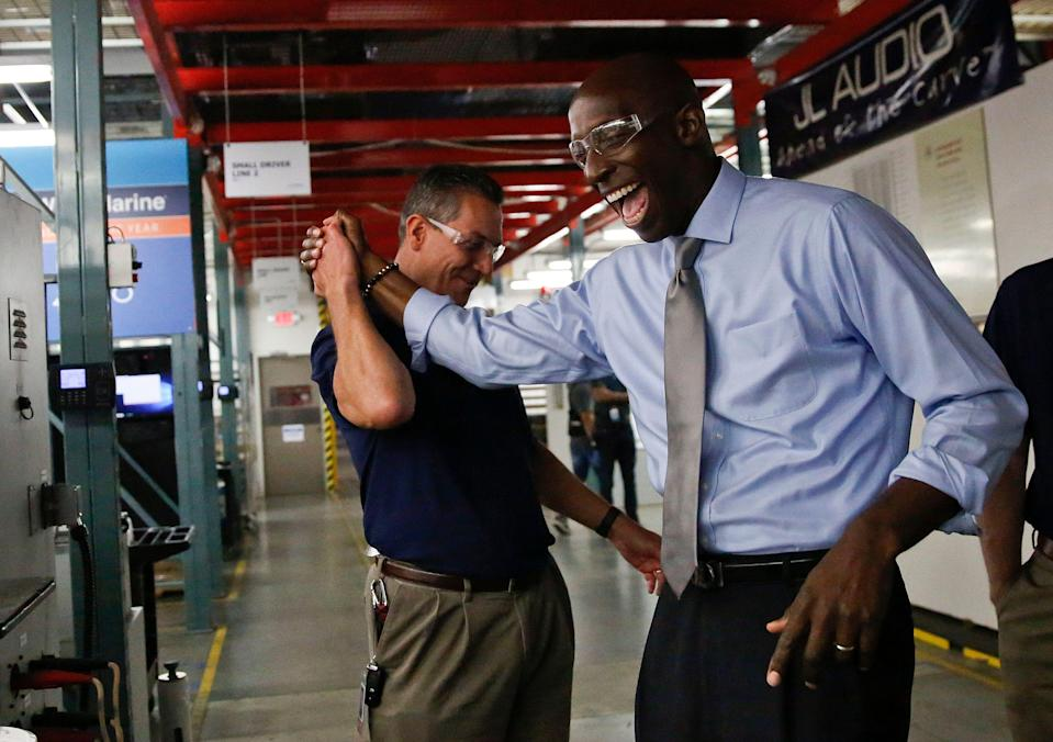 Miramar Mayor Wayne Messam, right, laughs with Stephen Turrisi, left, the director of training and technical services at JL Audio during a tour in Miramar, Fla. (Photo credit: Brynn Anderson)