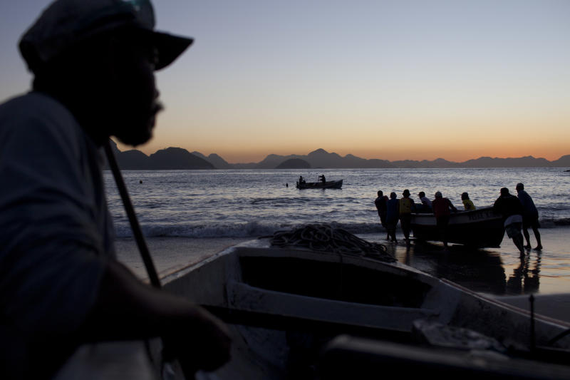 Fishermen and helpers push a boat to the water on Copacabana beach in Rio de Janeiro, Brazil, Thursday, Aug. 22, 2013. For as long as anybody can remember, the humble fishing boats have left each morning from their staked-out spot at one end of the sands, where they share space with scantily clad tourists on land and paddle surfers on water. (AP Photo/Felipe Dana)