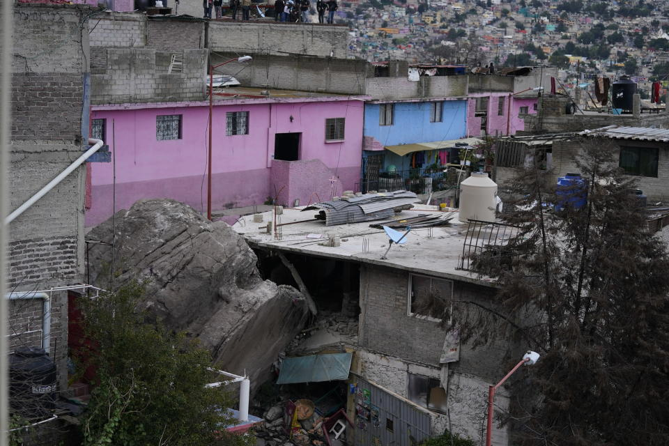 A boulder that plunged from a mountainside rests among homes in Tlalnepantla, on the outskirts of Mexico City, when a mountain gave way on Friday, Sept. 10, 2021. A section of mountain on the outskirts of Mexico City gave way Friday, plunging rocks the size of small homes onto a densely populated neighborhood and leaving at least one person dead and 10 others missing. (AP Photo/Eduardo Verdugo)