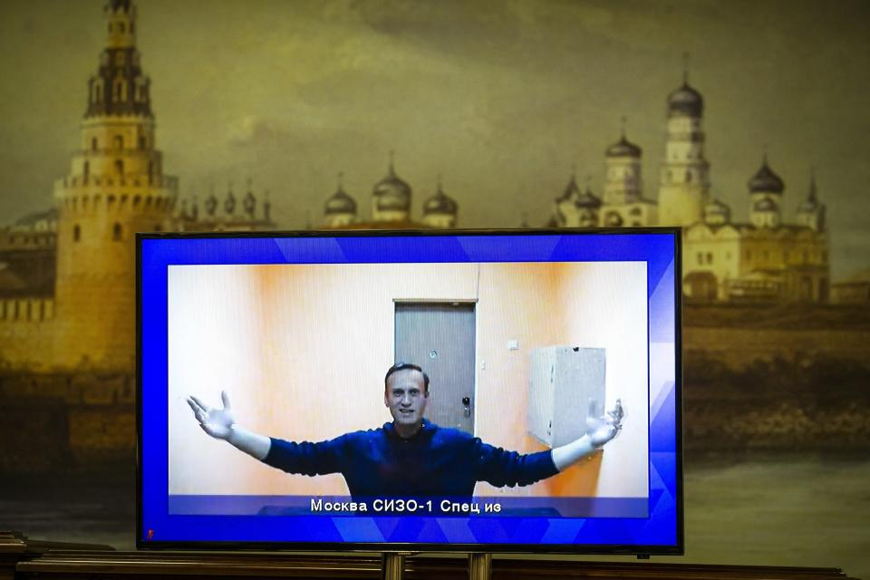 FILE - In this Jan. 28, 2021, file photo, Russian opposition leader Alexei Navalny appears on a TV screen during a court hearing appealing his jailing, with an image of the Kremlin in the background in Moscow, Russia. Navalny was jailed when he arrived in Moscow on Jan. 17, after authorities accused him of violating the terms of his parole on a 2014 fraud conviction. (AP Photo/Alexander Zemlianichenko, File)