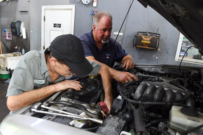 Bobby Ford (right) looks under the hood of a vehicle with longtime employee Greg Snead on Wednesday, Sept. 1, 2021, at Ford's automotive shop, Bobby's Auto Service Center, in Vero Beach. Several employees at the shop became infected with COVID-19, including Ford, who was vaccinated, and his twin brother, Billy Ford, who was not vaccinated. Eventually, Billy Ford had to be admitted to the hospital, sedated and put on a ventilator. Billy Ford died Aug. 14, leaving behind a wife, three children, his mother and three brothers.