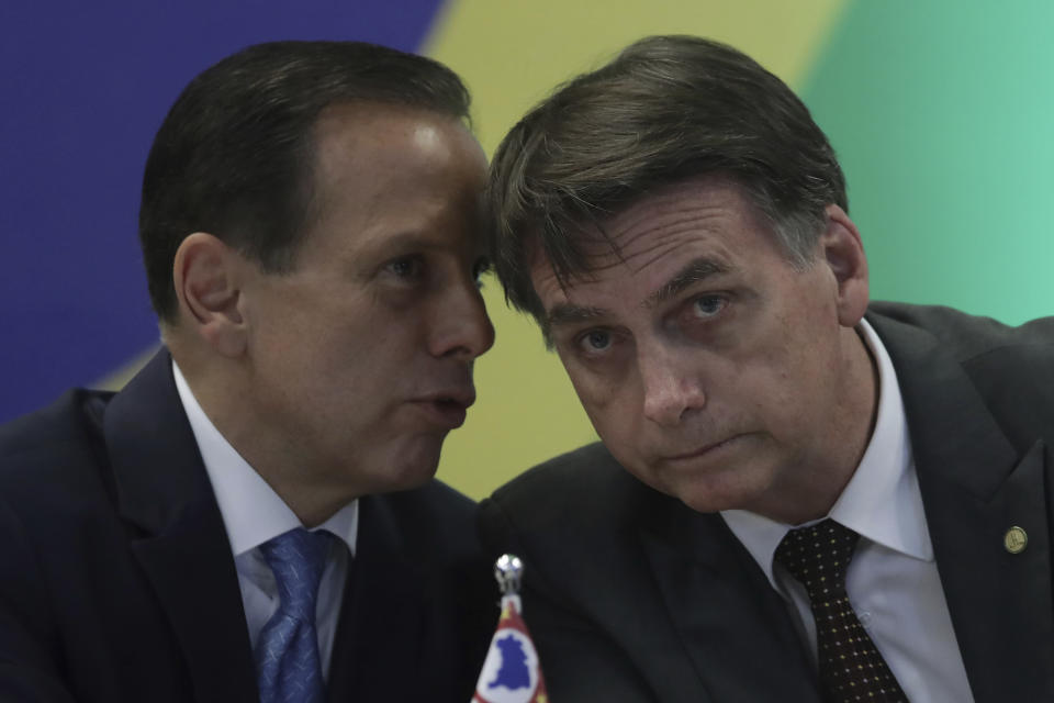 Brazil's President-elect Jair Bolsonaro, left, listens to Sao Paulo's Governor-elect Joao Doria, during a meeting with the Governors-Elect Forum, in Brasilia, Brazil, Wednesday, Nov. 14, 2018. Bolsonaro will be sworn in on Jan. 1. (AP Photo/Eraldo Peres)