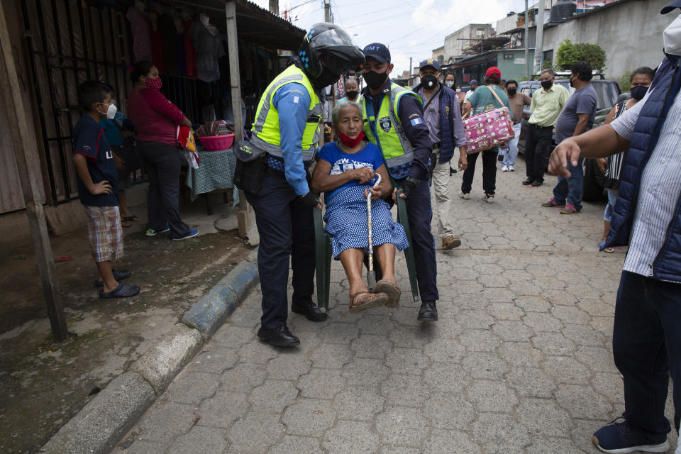 An elderly woman is carried by transit police to an area where city employees and volunteers are handing out free meals, in the Peronia neighborhood of Villa Nueva, Guatemala, Friday, July 24, 2020. The Villa Nueva City Hall delivers hot meals three times a week in a selected area of the neighborhood for residents who have been economically affected by the COVID-19 restrictions related to the government-ordered shutdowns. (AP Photo/Moises Castillo)