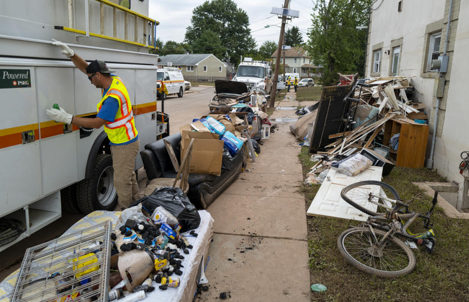 Utility workers work among debris from flood damage caused by the remnants of Hurricane Ida on a street in Manville, N.J., Sunday, Sept. 5, 2021. Flood-stricken families and business owners across the Northeast are hauling waterlogged belongings to the curb and scraping away noxious mud as cleanup from Ida moves into high gear. (AP Photo/Craig Ruttle)