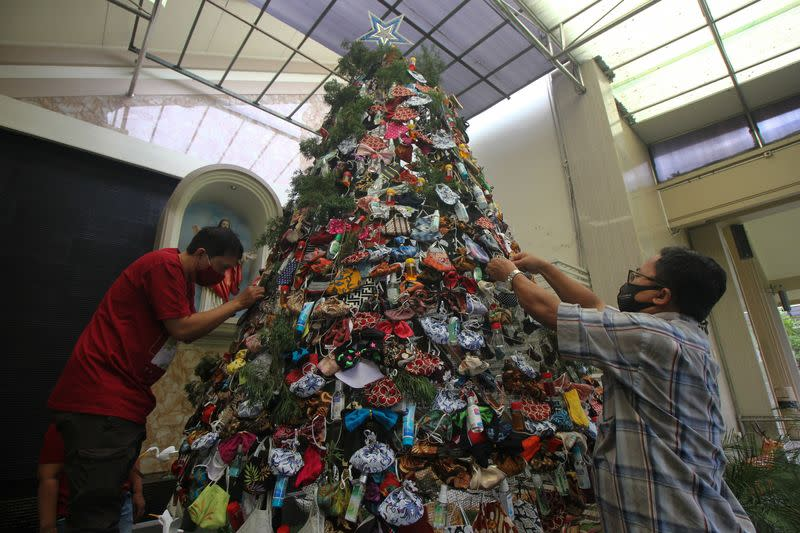 Men decorate a Christmas tree with masks and hand sanitizers at a church in Surabaya