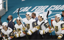 Vegas Golden Knights left wing Max Pacioretty (67), right wing Keegan Kolesar (55), center Nicolas Roy (10), right wing Ryan Reaves (75) and left wing William Carrier (28) react on the bench after center Jonathan Marchessault (not shown) scored against the San Jose Sharks during the first period of an NHL hockey game in San Jose, Calif., Saturday, Feb. 13, 2021. (AP Photo/Josie Lepe)