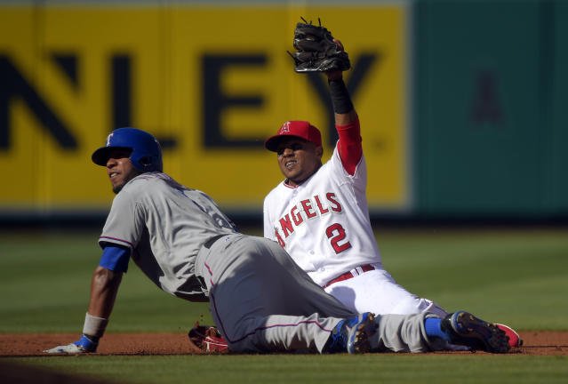 Los Angeles Angels shortstop Erick Aybar, right, holds up his glove after tagging out Texas Rangers' Elvis Andrus as Andrus tried to stretch a single into a double during the first inning of a baseball game, Sunday, June 22, 2014, in Anaheim, Calif. (AP Photo/Mark J. Terrill)