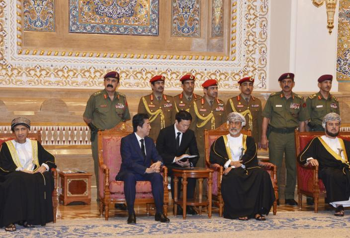 In this photo made available by Oman News Agency, Oman's Sultan Haitham bin Tariq Al Said, center right, receives Japan's prime minister Shinzo Abe after his arrival in Muscat, Oman, Tuesday, Jan. 14, 2020.(Oman News Agency via AP)
