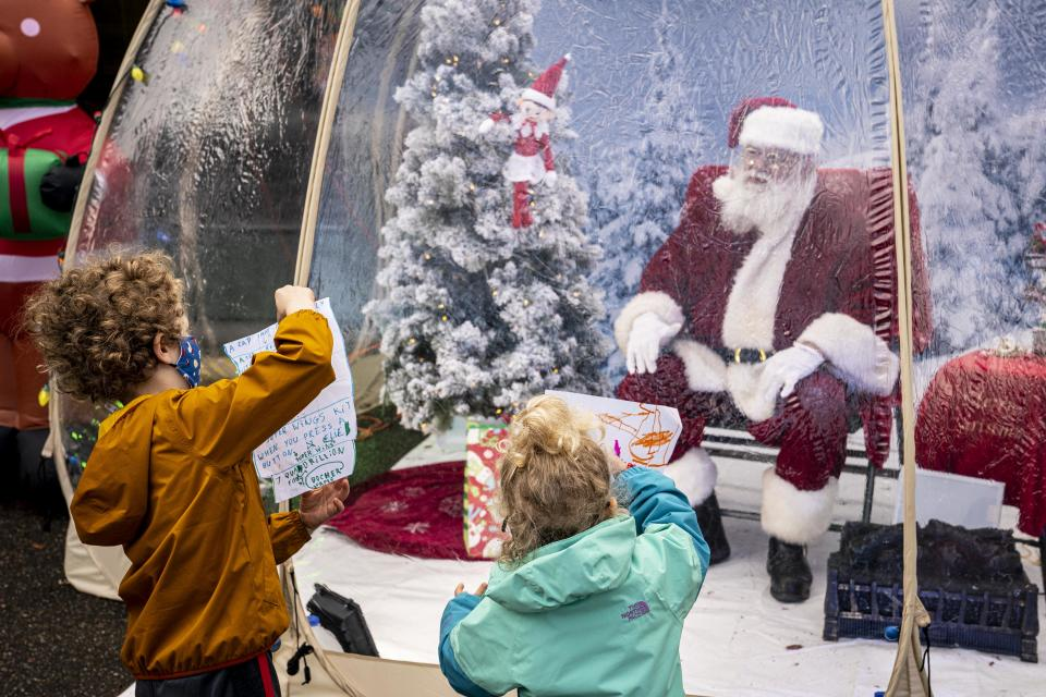 """Many Santas, including the """"Seattle Santa"""" pictured here, will be sitting in plastic snow globes or """"igloos"""" in order to ensure social distancing. (Photo: David Ryder/Getty Images)"""