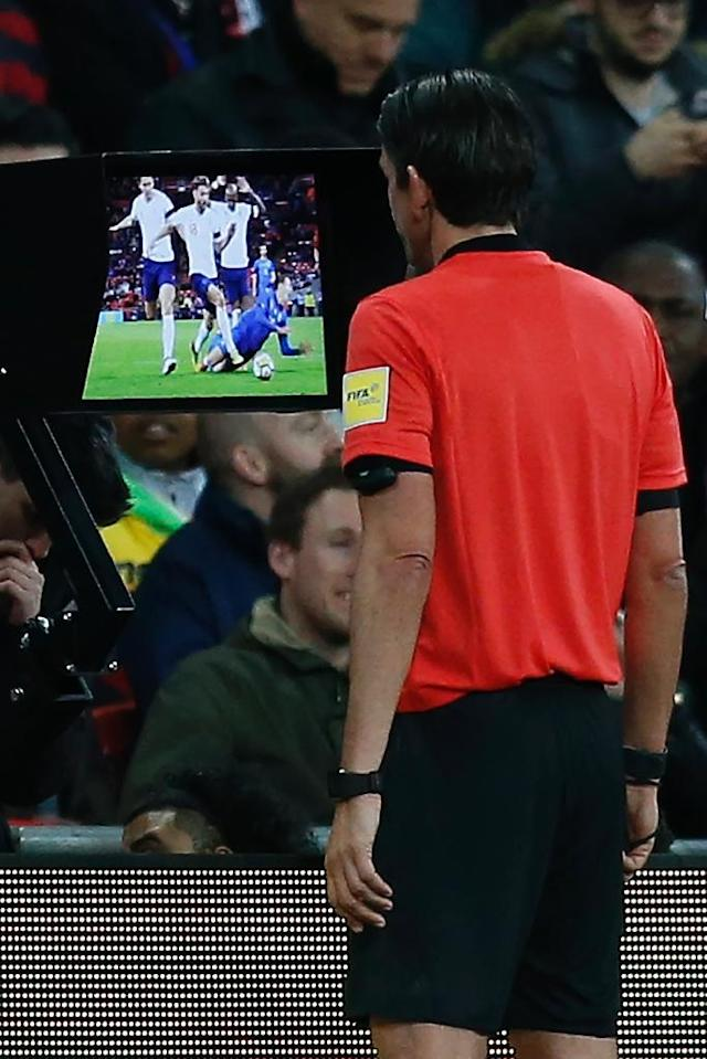 Deniz Aytekin watches images of an Italy penalty appeal on a screen by the pitch during their recent friendly against England (AFP Photo/Ian KINGTON)