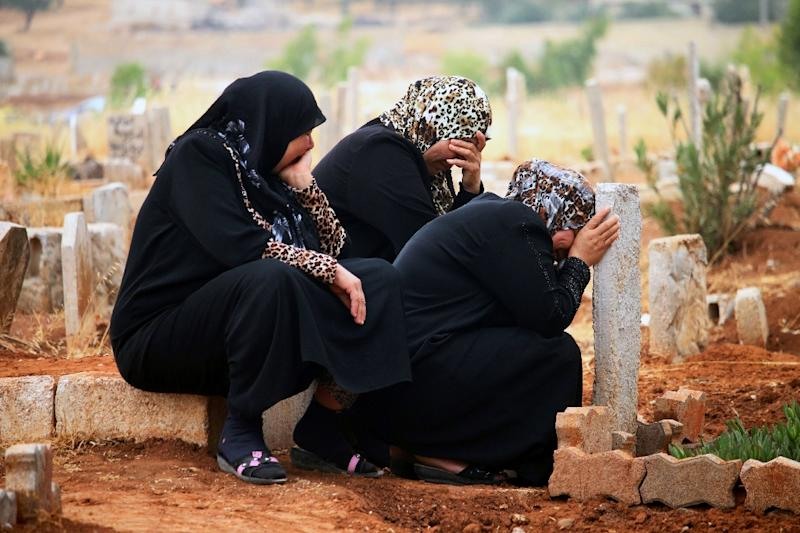 Syrian women mourn at the grave of a relative in the rebel-held area of Daraa on July 6, 2016 (AFP Photo/Mohamad Abazeed)
