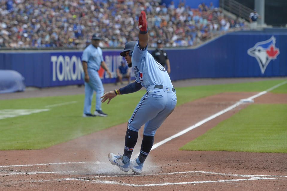 Toronto Blue Jays' Santiago Espinal scores a run against the Texas Rangers on a single by Bo Bichette during the third inning of the first baseball game of a doubleheader in Buffalo, N.Y., Sunday, July 18, 2021. (AP Photo/Adrian Kraus)