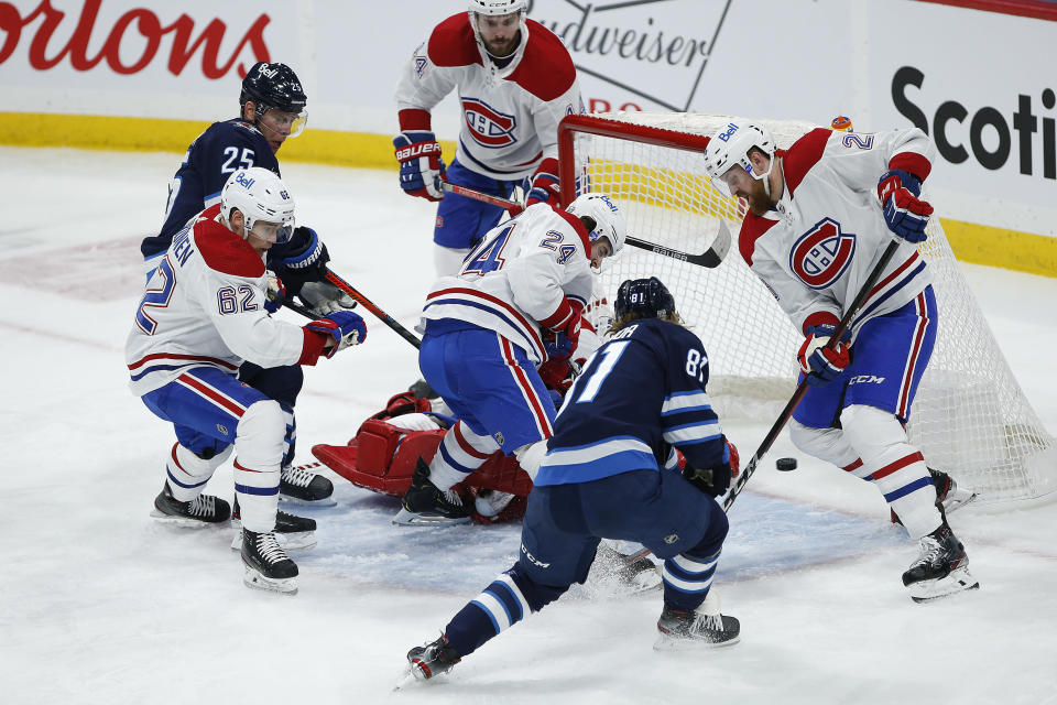 Winnipeg Jets' Kyle Connor (81) scores against Montreal Canadiens goaltender Carey Price, center bottom, during second-period NHL hockey game action in Winnipeg, Manitoba, Thursday, Feb. 25, 2021. (John Woods/The Canadian Press via AP)