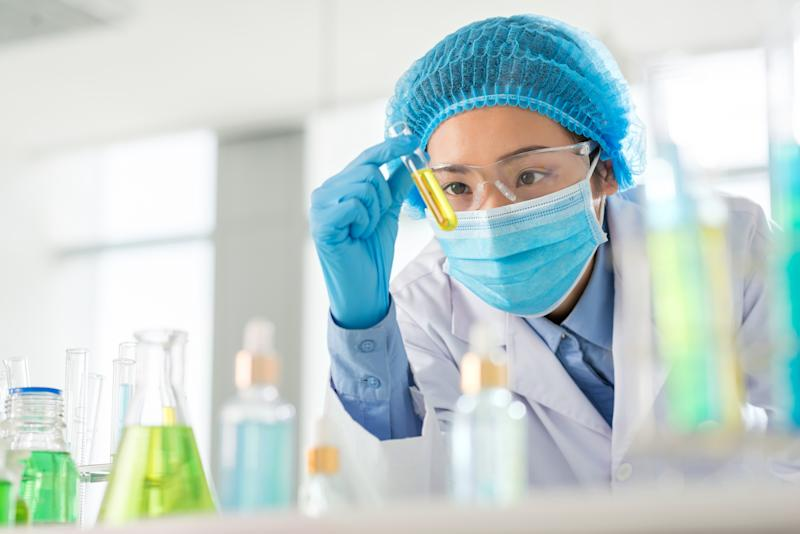 Lab worker holding a vial containing a yellow liquid.