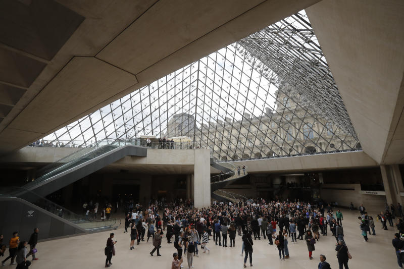 Le Louvre museum employees and tourist gather under the giant glass pyramid by late architect I.M. Pei, Friday, May 17, 2019 in Paris. Pei died earlier this week at the age of 102. (AP Photo/Michel Euler)
