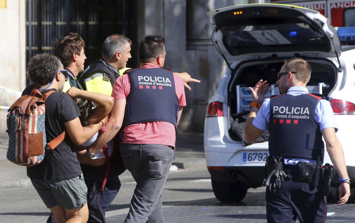An injured person is carried in Barcelona, Spain, Aug. 17, 2017, after a white van jumped the sidewalk in a historic district, crashing into a summer crowd. (Oriol Duran/AP)