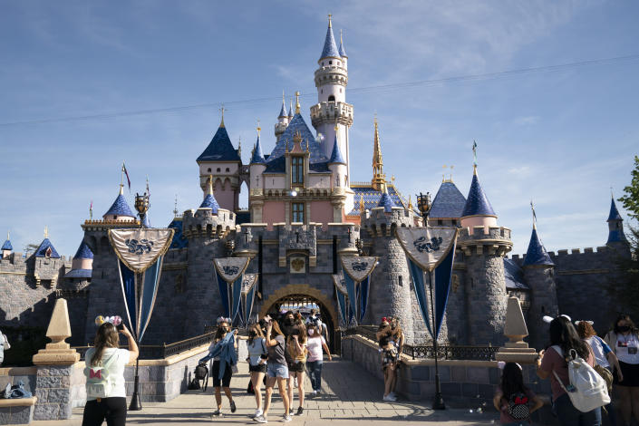 """FILE - In this Friday, April 30, 2021, file photo, visitors exit The Sleeping Beauty Castle at Disneyland in Anaheim, Calif. California will offer six """"dream vacation"""" incentives to spur more people to get coronavirus vaccinations, California Gov. Gavin Newsom said Monday, June 14, 2021, on the eve of the state's awarding of $15 million in cash prizes. Goodies in the package include floor seats at an NBA game with the LA Lakers, and tickets to Disneyland, Legoland, SeaWorld and a symphony, he said. (AP Photo/Jae C. Hong, File)"""