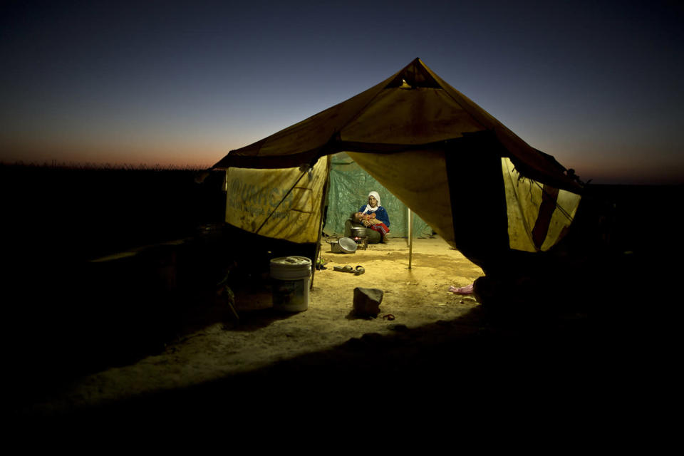<p>A Syrian refugee woman tends to her daughter while cooking inside her tent at an informal tented settlement near the Syrian border on the outskirts of Mafraq, Jordan, Aug. 26, 2015. (Photo: Muhammed Muheisen/AP) </p>