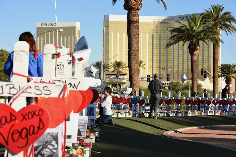 In this October 2017 photo take just days after the mass shooting in Las Vegas, a woman prays beside 58 white crosses laid out in honor of for the victims those killed when a gunman opened fire from the 32nd floor of the Mandalay Bay hotel.